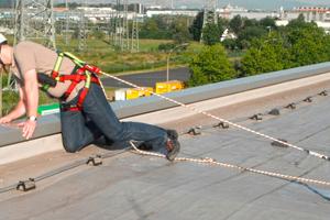 """Arbeiten am Dachrand mit sicherer PSAgA und Sicherung am Sekuranten<span class=""""bildnachweis"""">Foto: TÜV Rheinland</span>"""