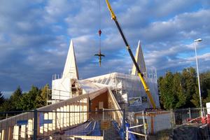 """Der Kirchenraum und die Zugangsrampe sind in Holzskelettbauweise in Kombination mit Holzrahmenbau errichtet. Bei der Dach- und den Turmkonstruktionen der Kirche kam BS-Holz zum Einsatz. Die Verbindungsbrücke bilden BS-Holz-Fachwerkbinder<span class=""""bildnachweis"""">Foto: Holzbau Amann GmbH</span>"""